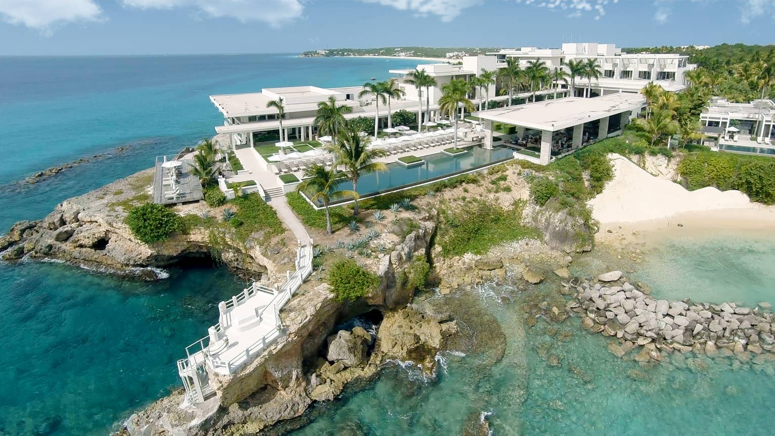 Aerial view of Four Seasons Resort Anguilla white buildings, pool, palm trees, rocky shore and white sand beach on ocean
