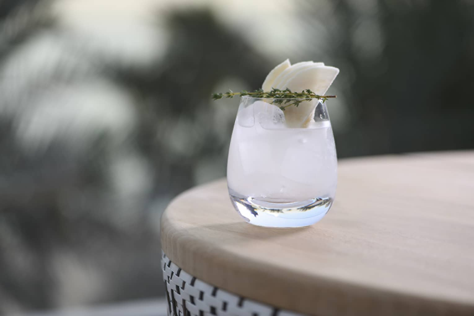 A short curved glass of a white cocktail garnished with a sprig of greenery and citrus on a round wooden table