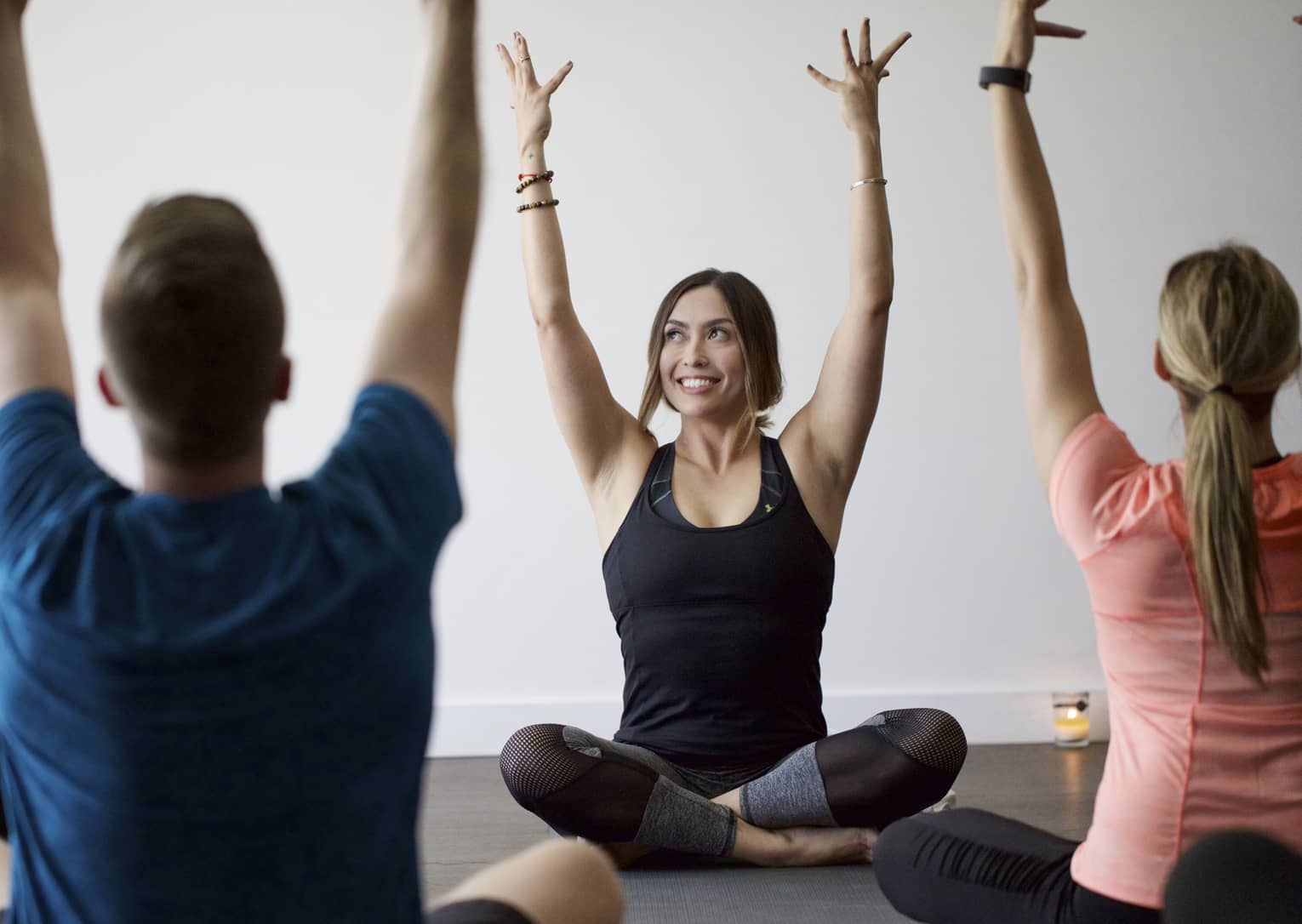 Man, woman sit in front of smiling yoga instructor, cross-legged with arms raised above head
