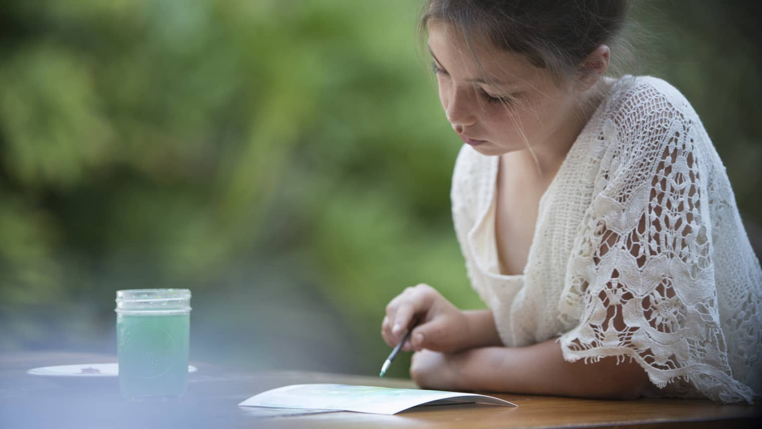 Girl painting on a piece of paper, a glass of blue-colored water next to her, trees in background