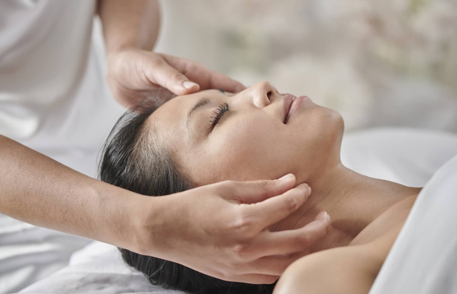 Masseuse massages woman's face as she lies face up on table under white sheet