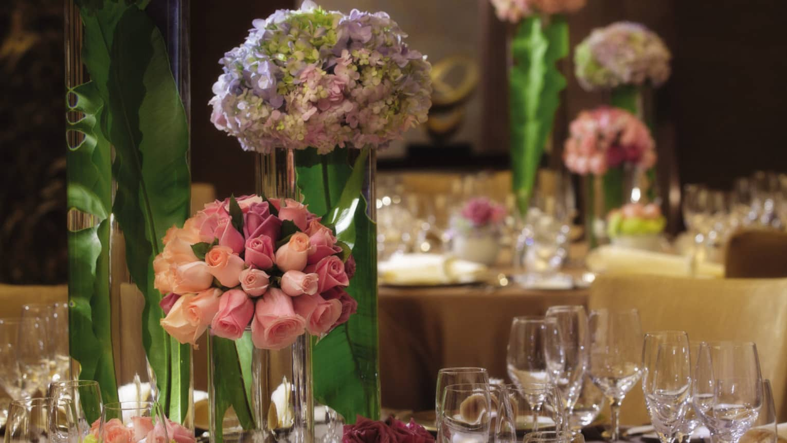 Pink roses in glass vase on formal dining banquet table