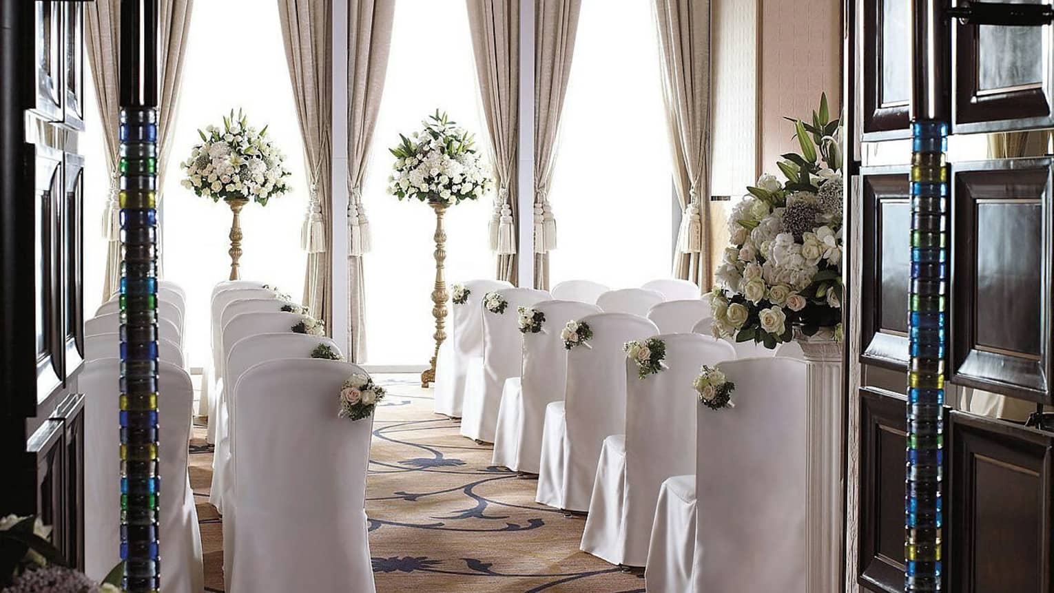 Ballroom wedding ceremony, rows of chairs with white linens face sunny window