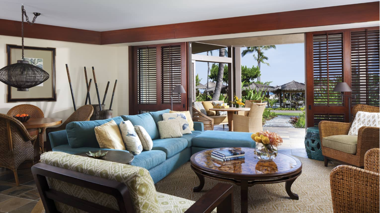 'Ohana Suite L-shaped blue sofa, chairs around table, open wood shutters to patio