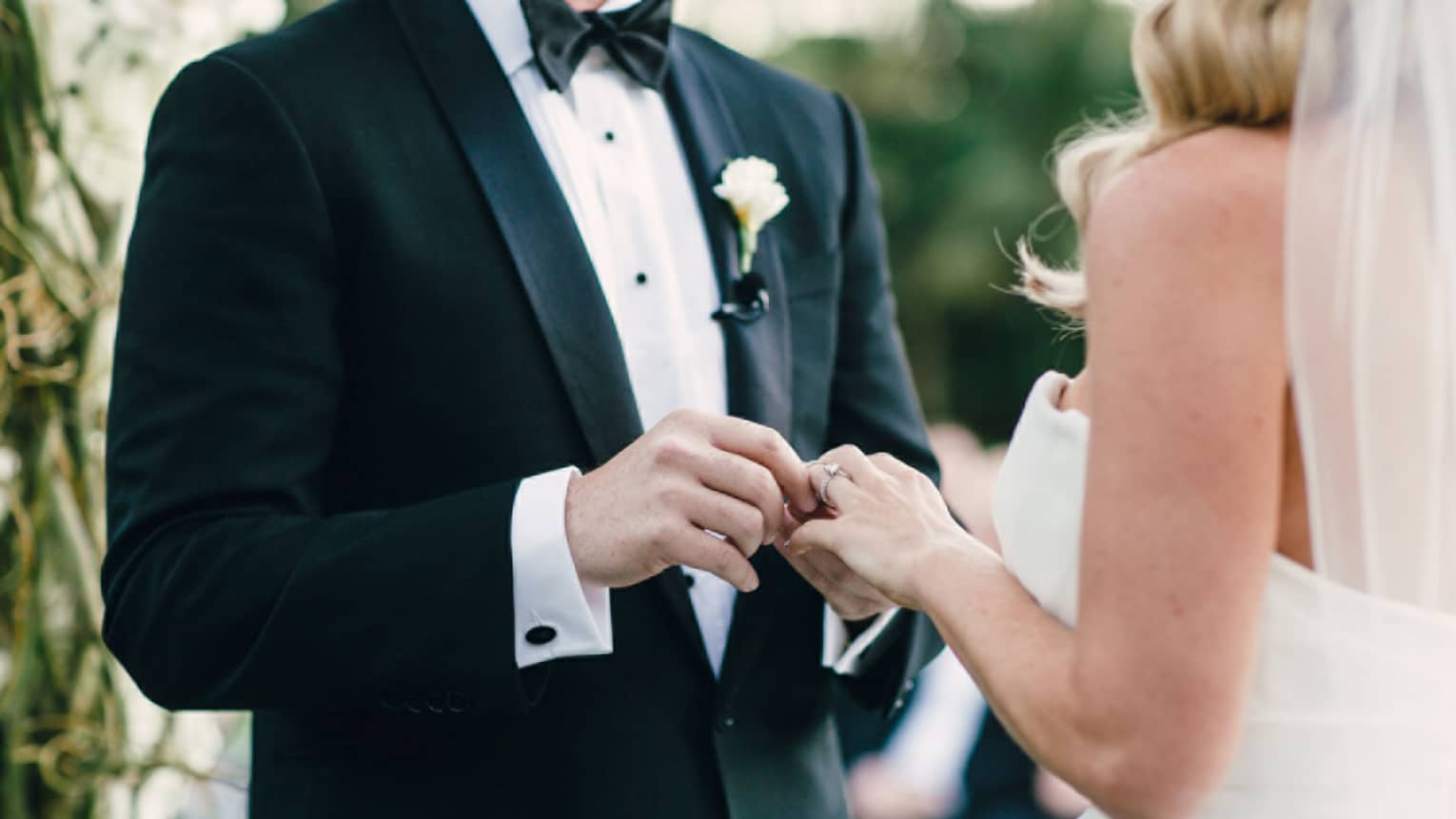 Groom slips wedding ring on bride's finger