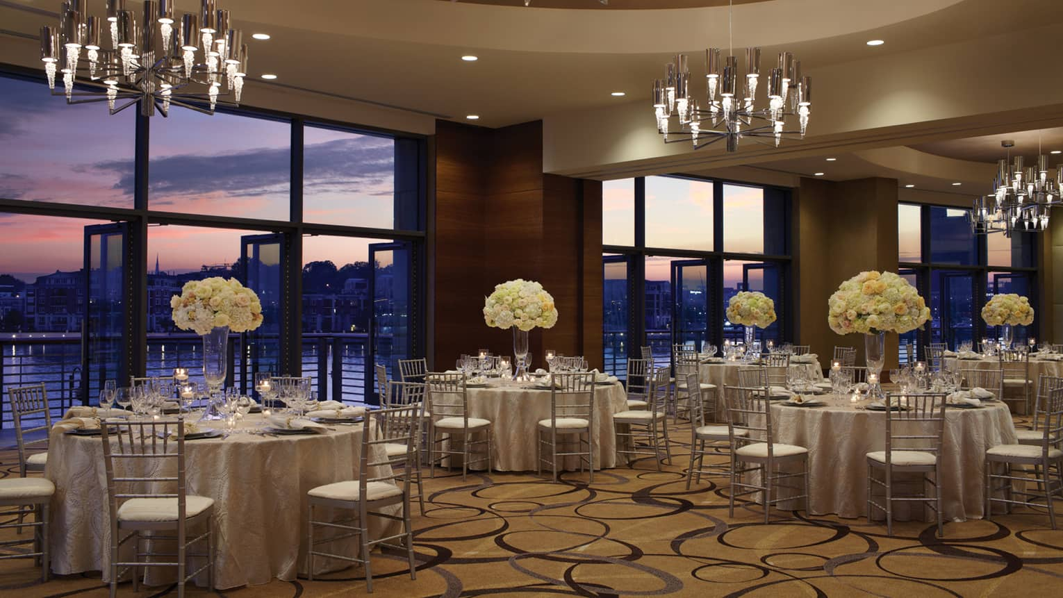 Ballroom banquet dining tables under chandeliers and large windows with sunset Harbor views