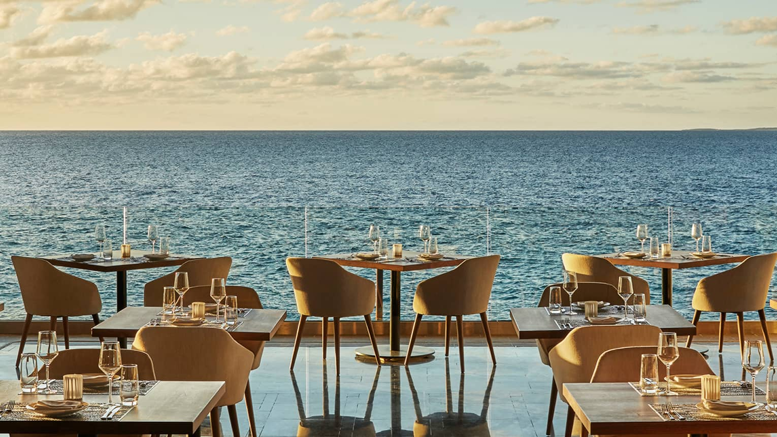 Dining tables, chairs for two in row along outdoor bar overlooking ocean