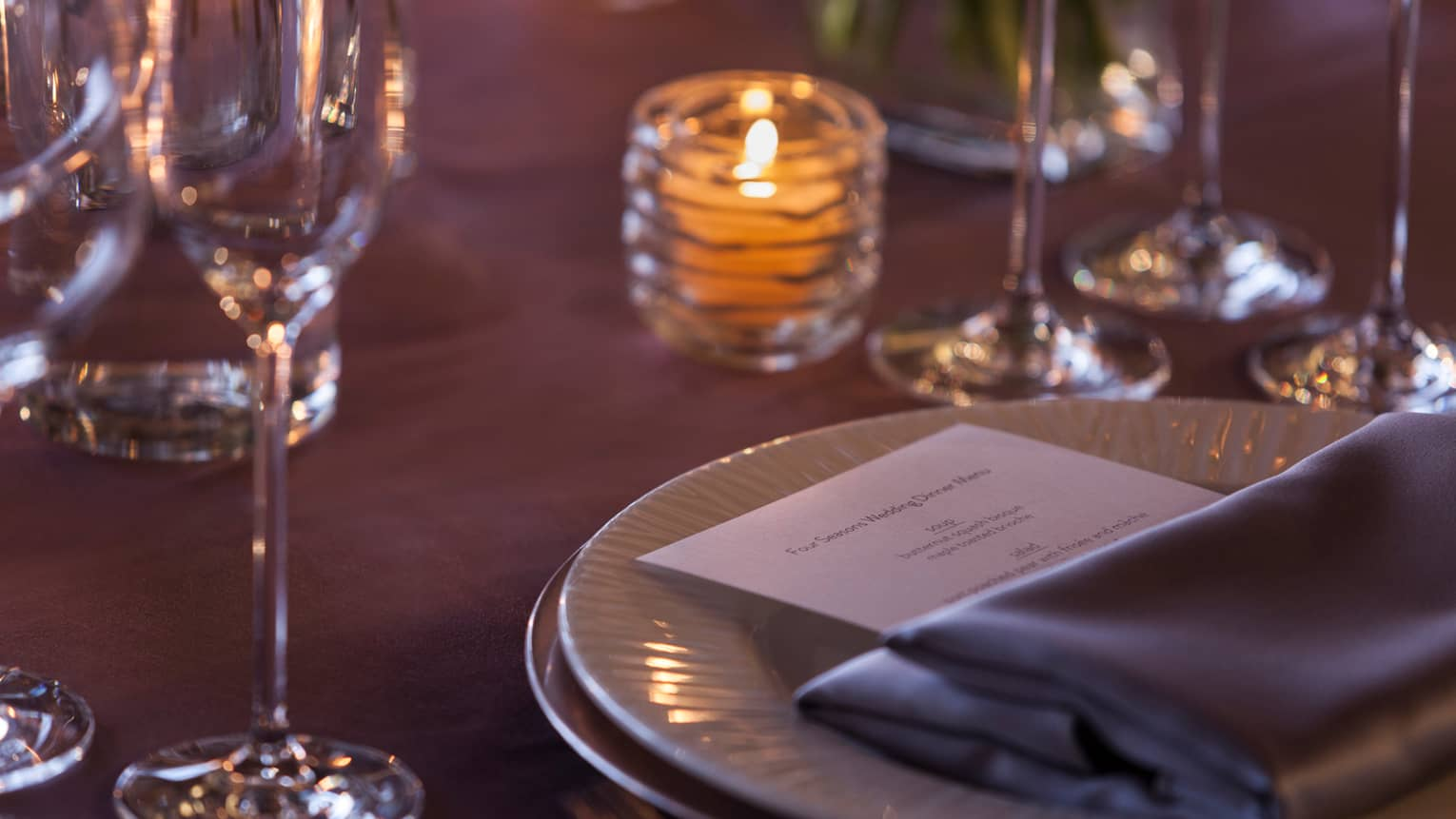 Close up of table with candle, grey napkin and dinner menu on white plate, glasses