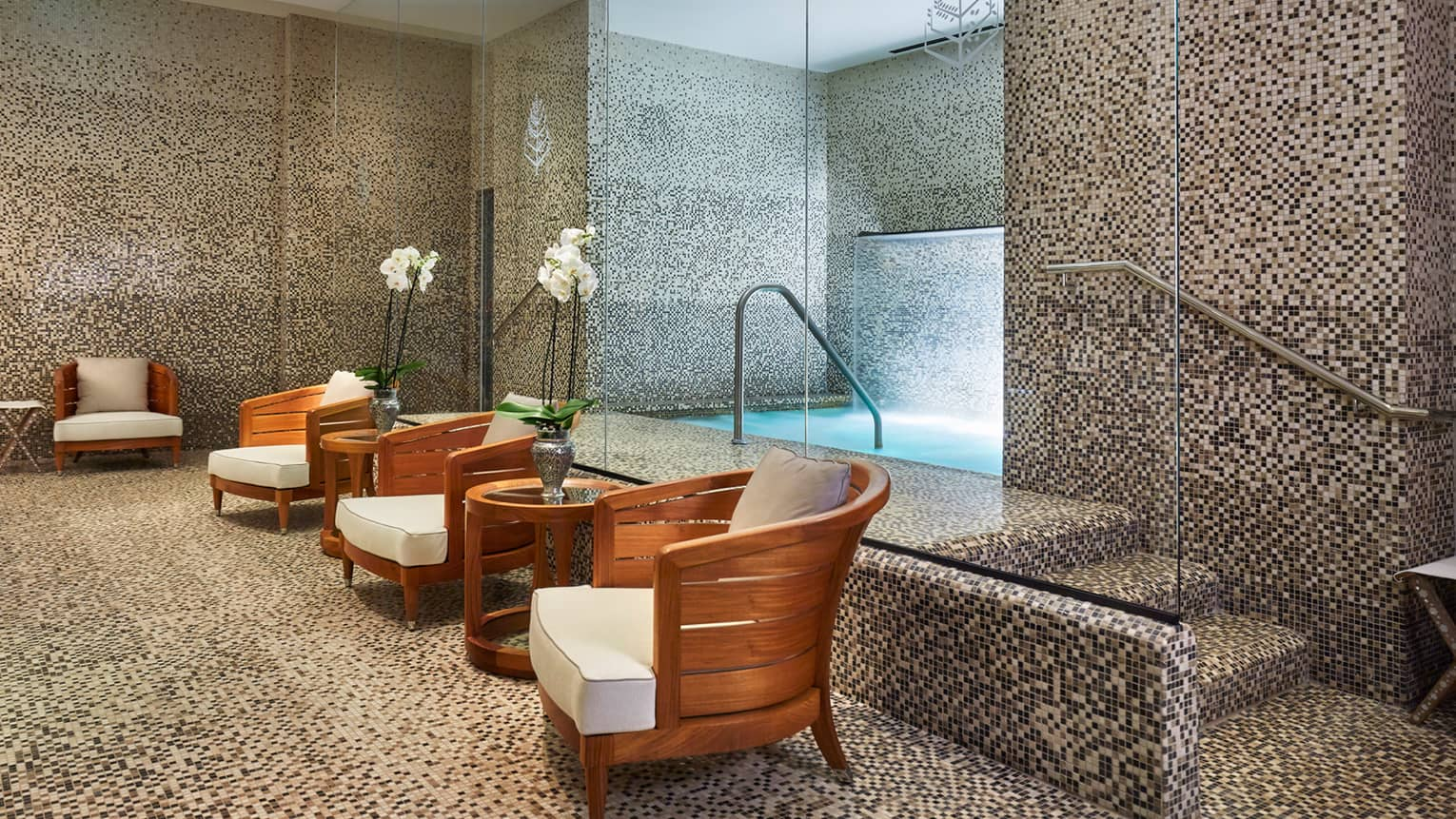 Tile spa room with whirlpool bath behind row of wood chairs with white cushions, tables with white orchids