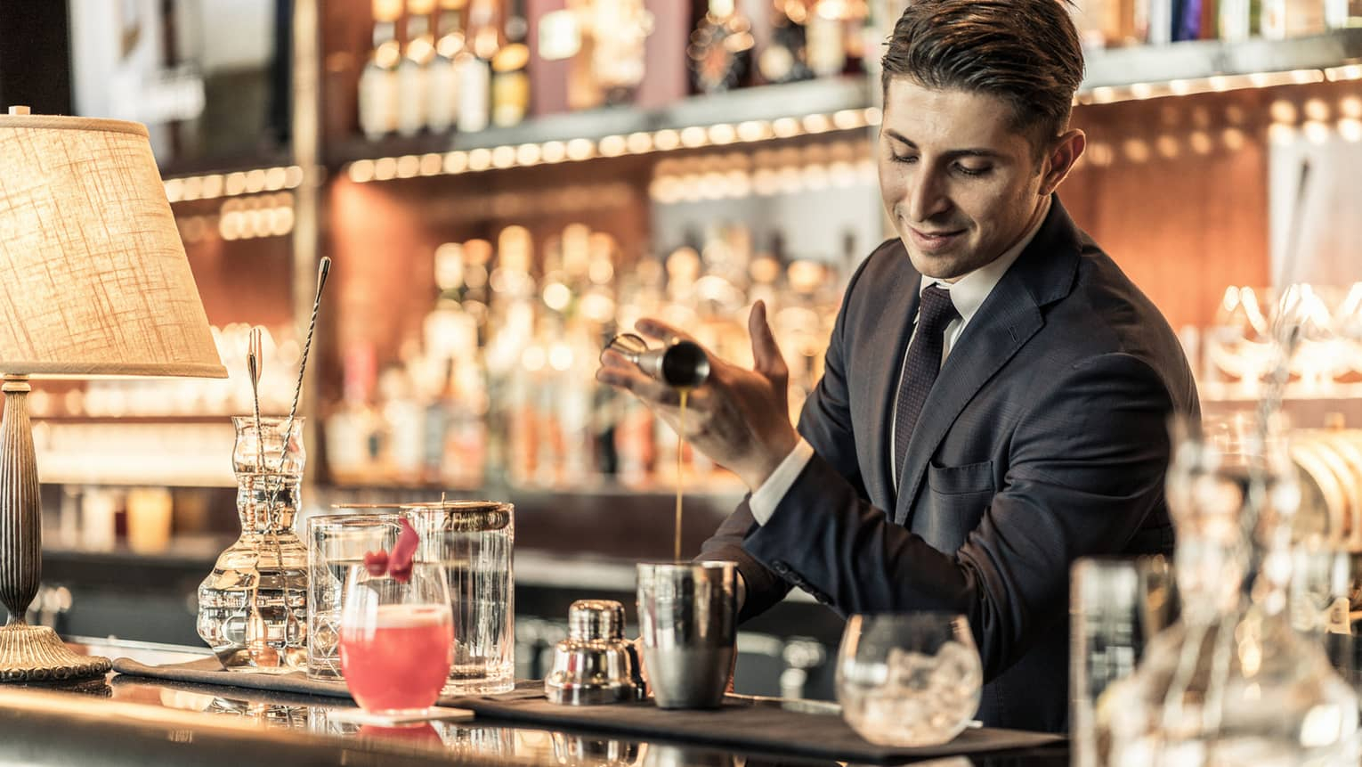 Bartender behind bar, pouring liquid from jigger into metal shaker among bar accessories