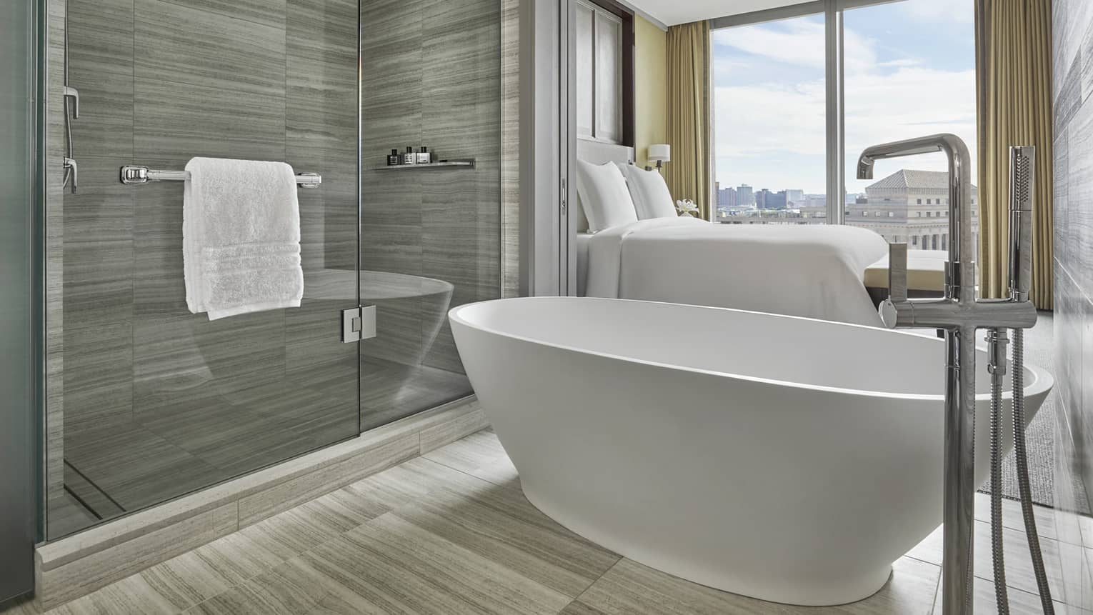 free standing tub and glass paneled walk in shower in a hotel bathroom