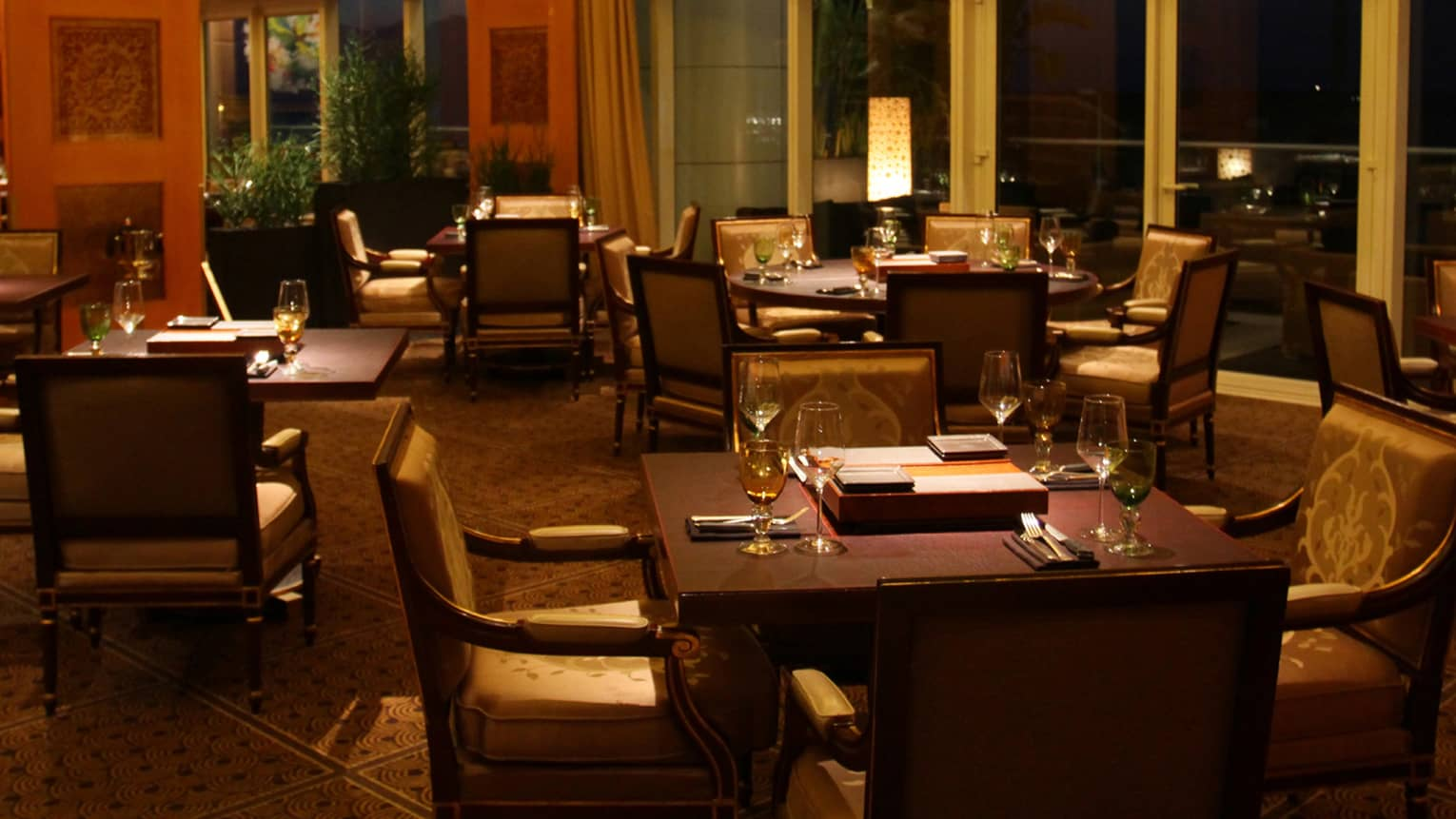 Dimly lit dining room of restaurant, brown square tables, each with four arm chairs, windows