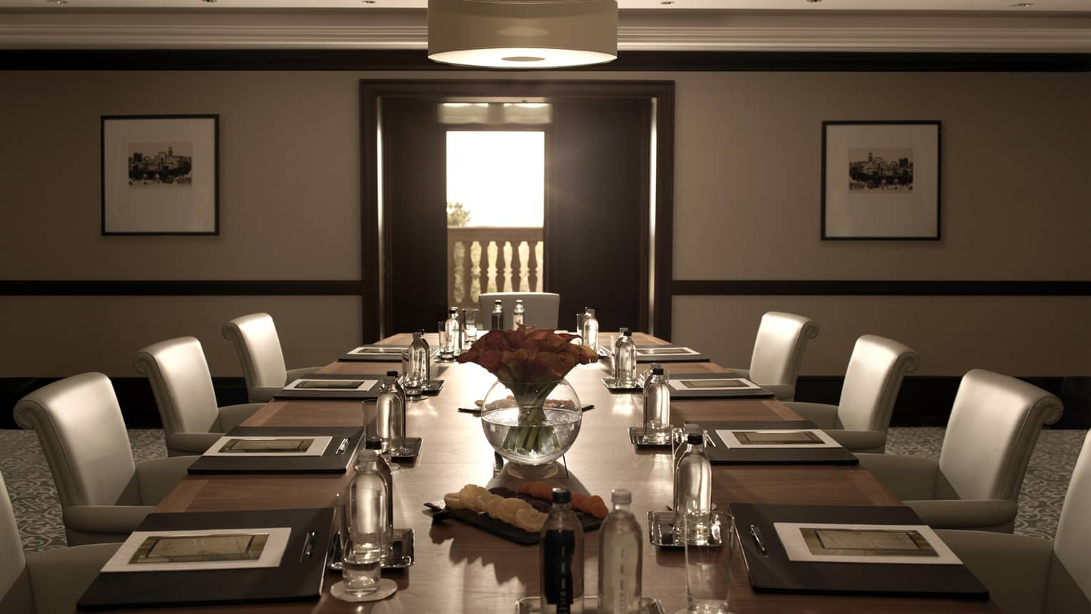 Sleek leather chairs around large, dark wood boardroom table set for business event in Humayun Meeting Room