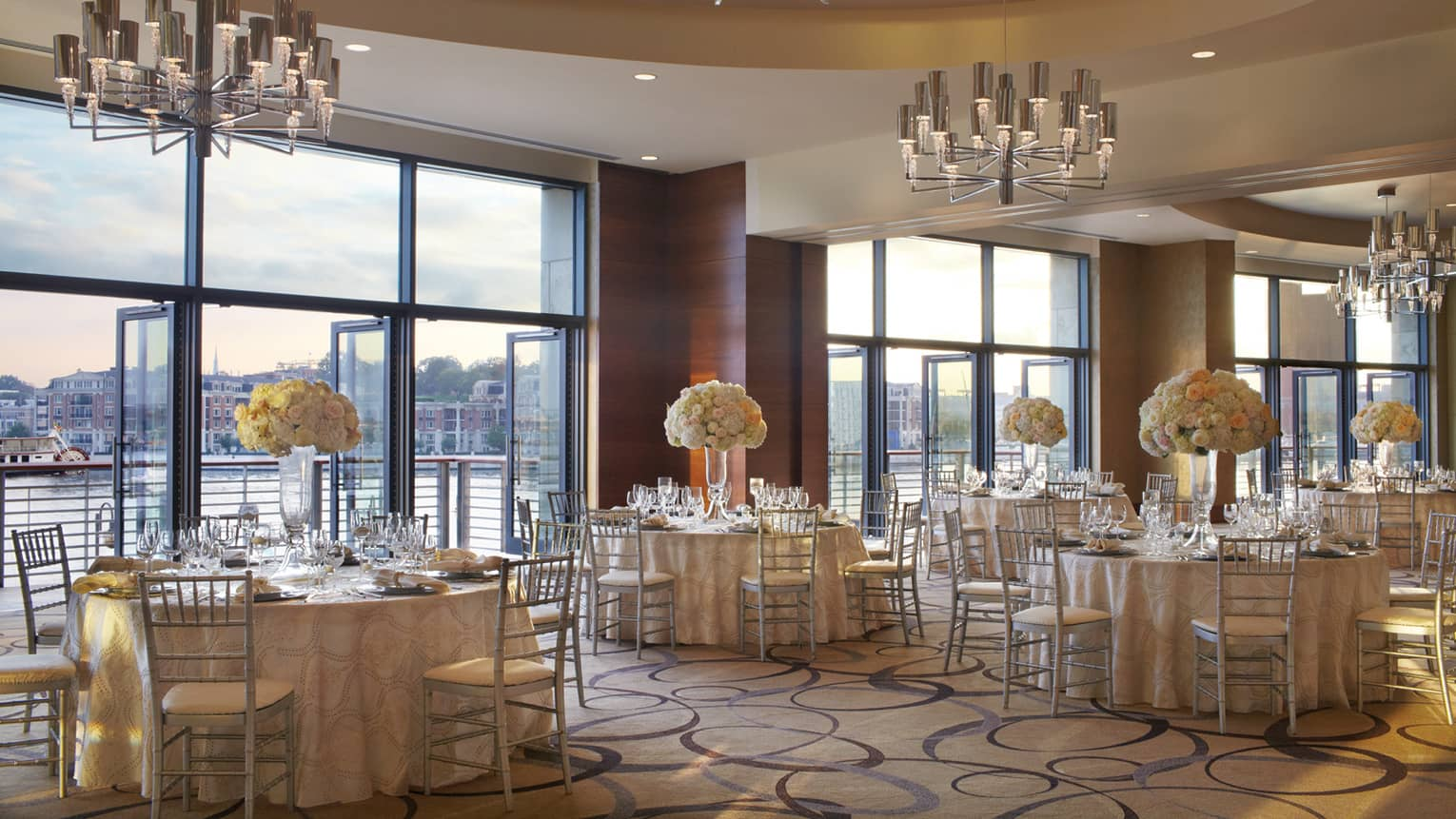Ballroom with elegant round banquet tables by open air floor-to-ceiling windows overlooking Harbor East water