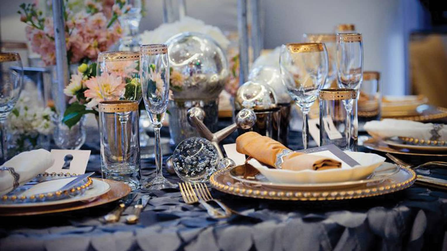 Close-up of banquet dining table setting with gold-rimmed glassware and plates, roses