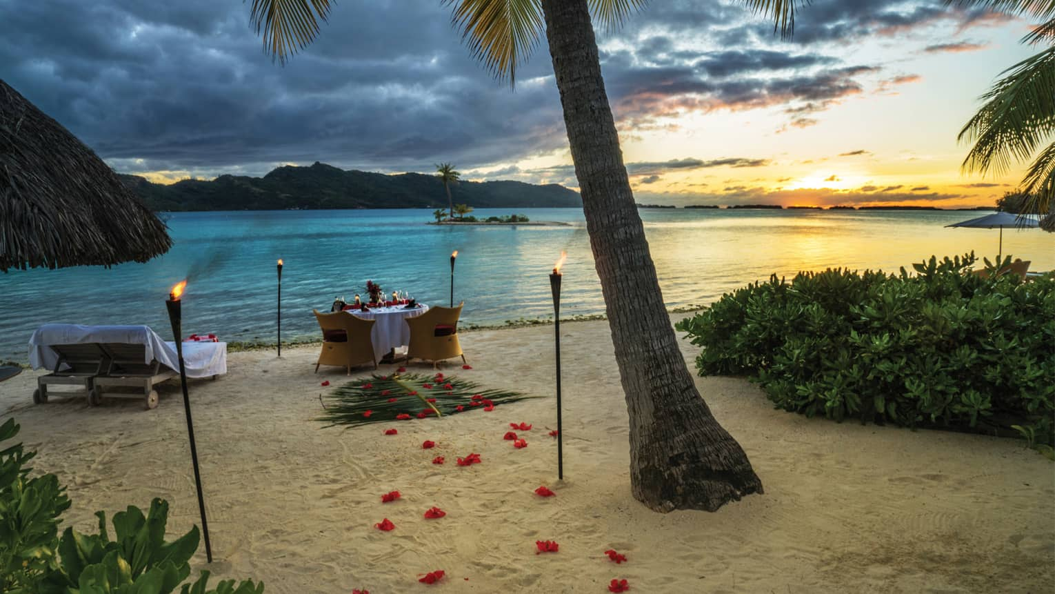 Rose petals and torches lead to a candlelit dinner table on the white sand beach by shore  at sunset