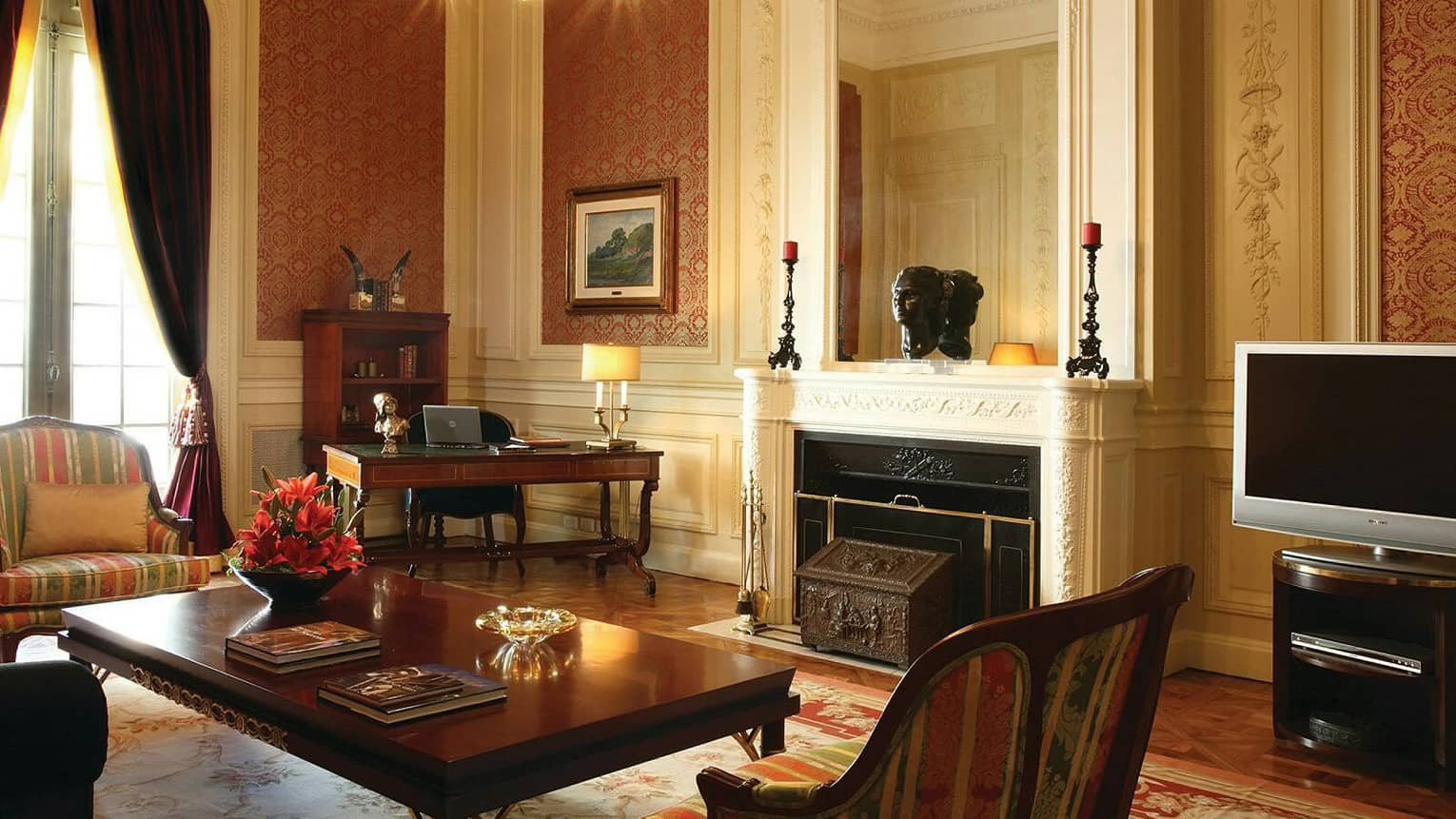 La Mansión Royale Suite living room with white fireplace mantel, dark wood furniture, Old World decor