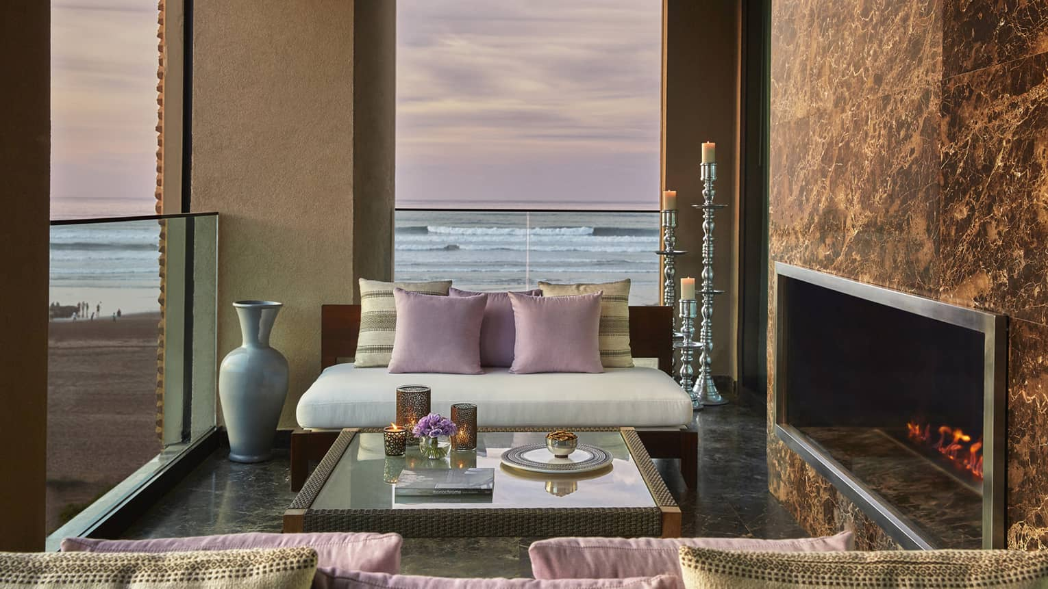 Royal Suite Ocean View white sofa, pink pillows by fireplace, under window with pink sunset, ocean