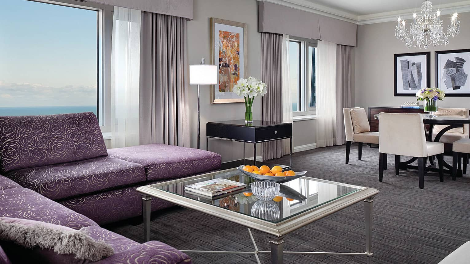 Hotel room with L-shaped velvet purple sofa with rose pattern, coffee table with bowl of fresh oranges, dining table, crystal chandelier