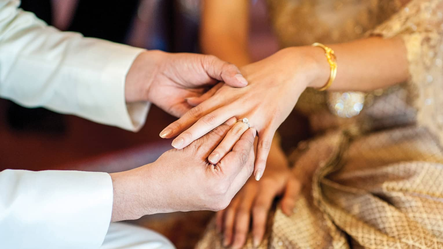 Groom slips wedding ring onto bride's finger