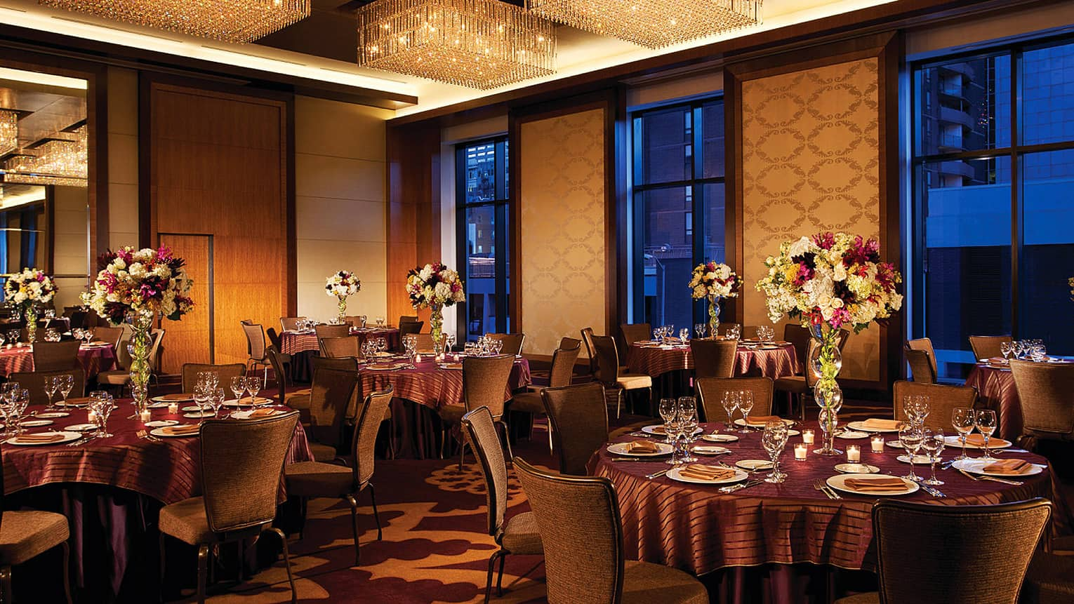 Grand Ballroom event at night with elegant banquet tables, purple and white flowers and ceiling with lights