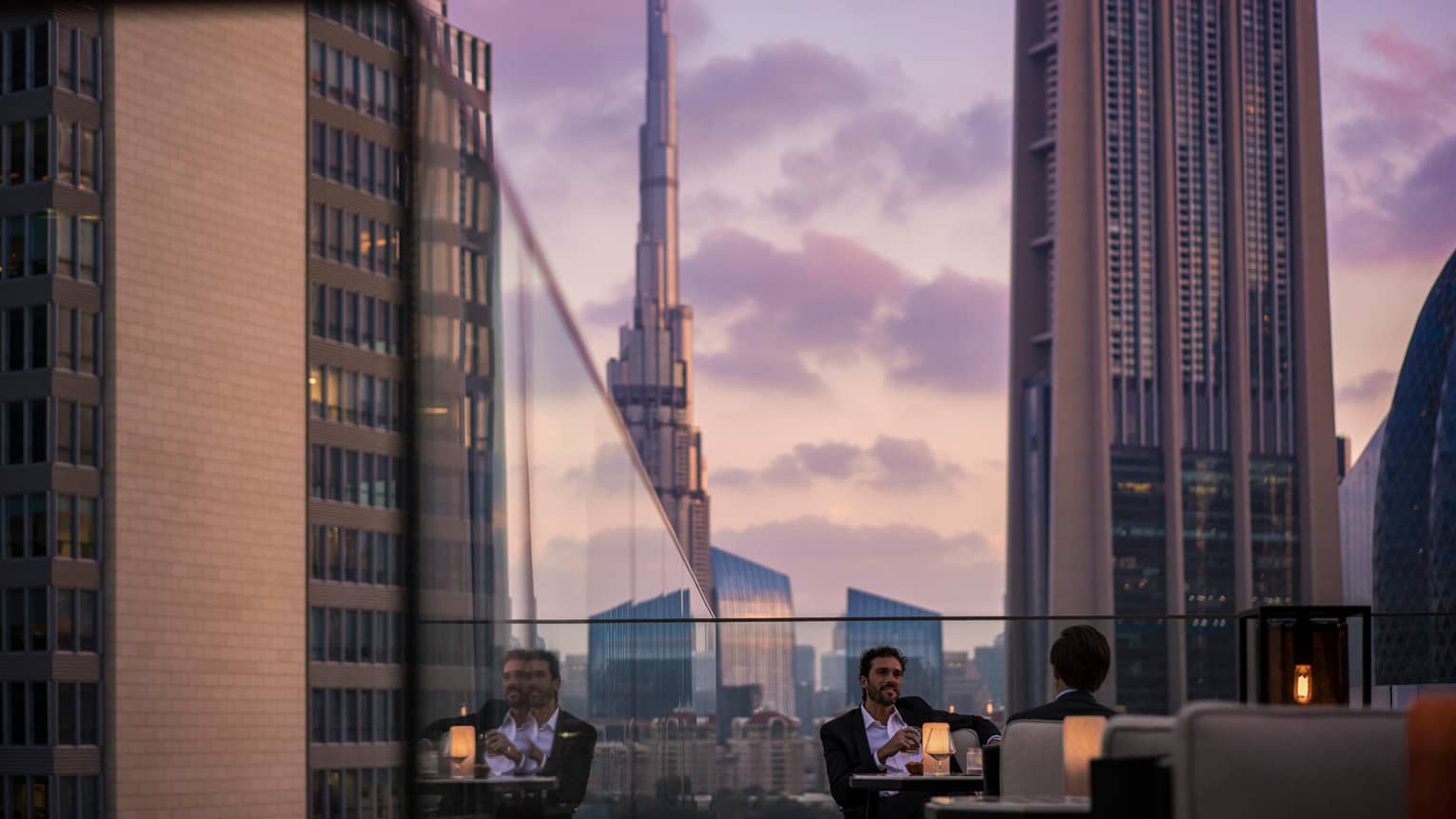 Men in suits on rooftop patio in front of glass balcony wall overlooking city at sunset