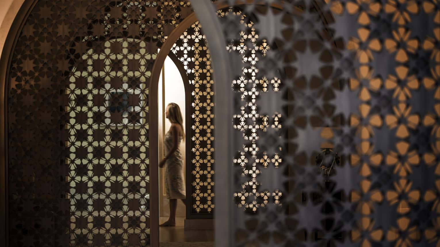 Woman in white wrap walks through dimly-lit decorative entranceway in hall