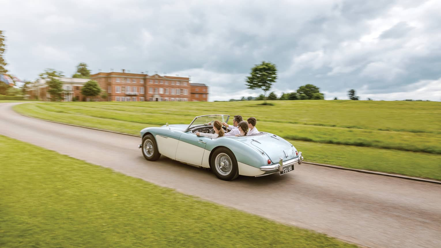Family rides in vintage convertible car down road past English countryside to hotel manor