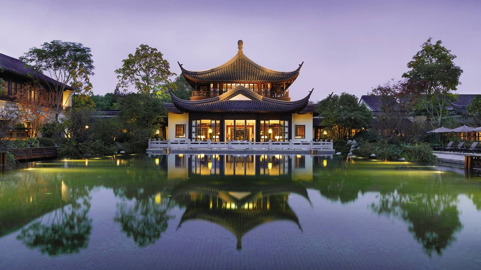 Four Seasons Hotel Hangzhou exterior, reflection in large pool at dusk