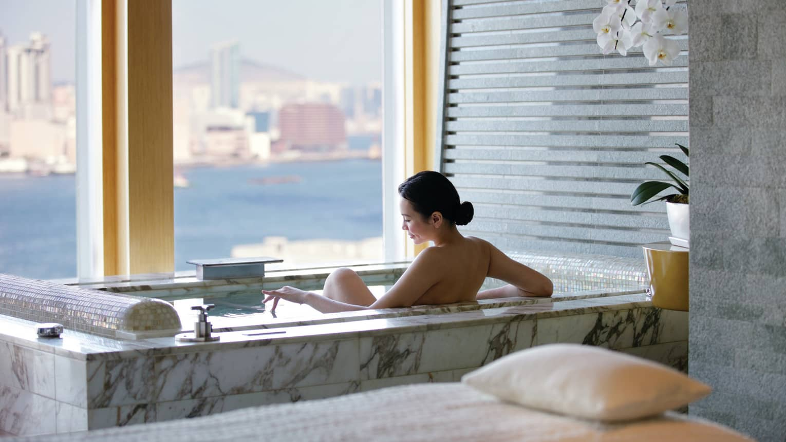 Woman's bare back above marble spa tub in tile bathroom by window with water, city views