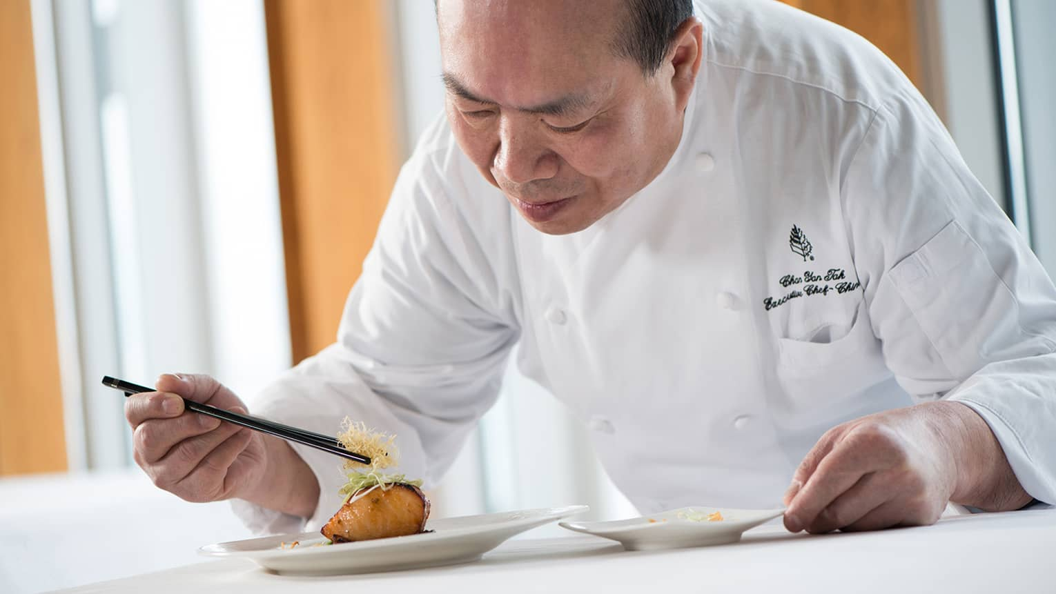Chef in white uniform leans over grilled salmon dish on plate, adds garnish with chopsticks