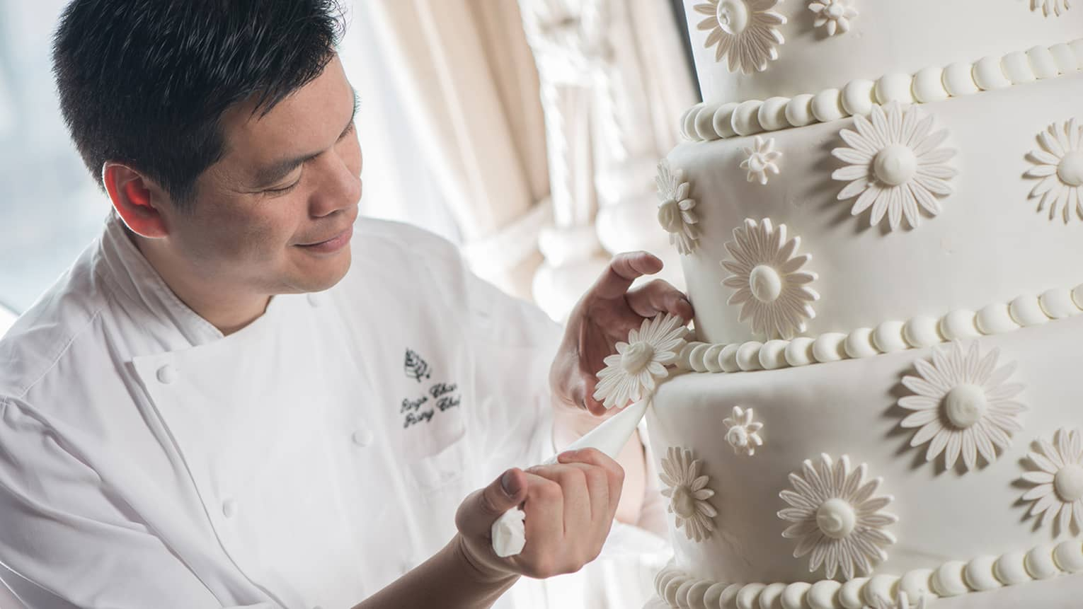 Pastry Chef Ringo Chan decorates icing of large tiered wedding cake