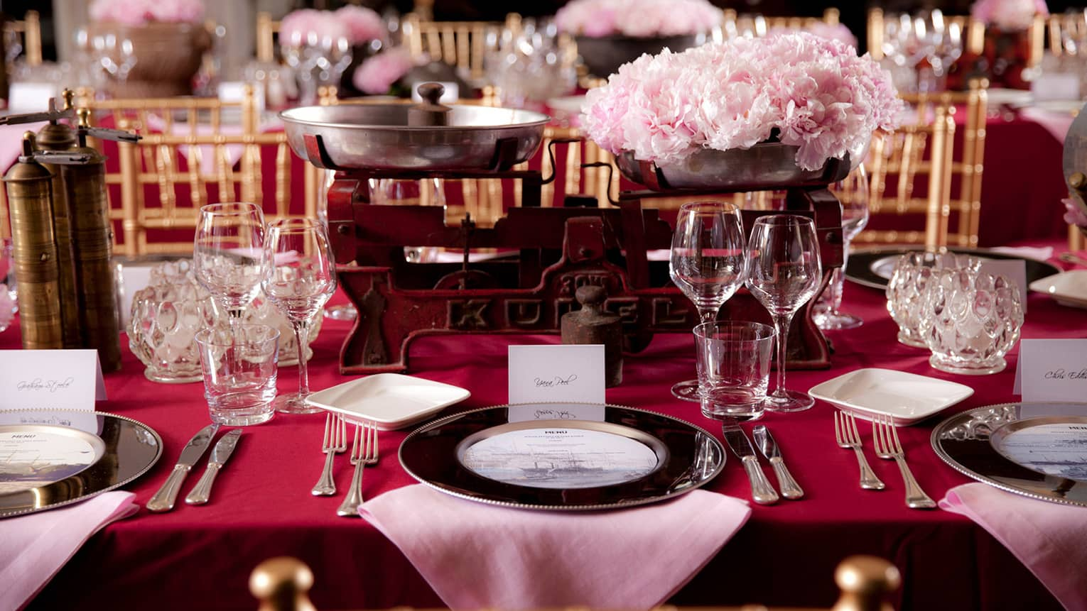 Close-up of banquet dining table with red tablecloth, pink flowers in antique iron holders
