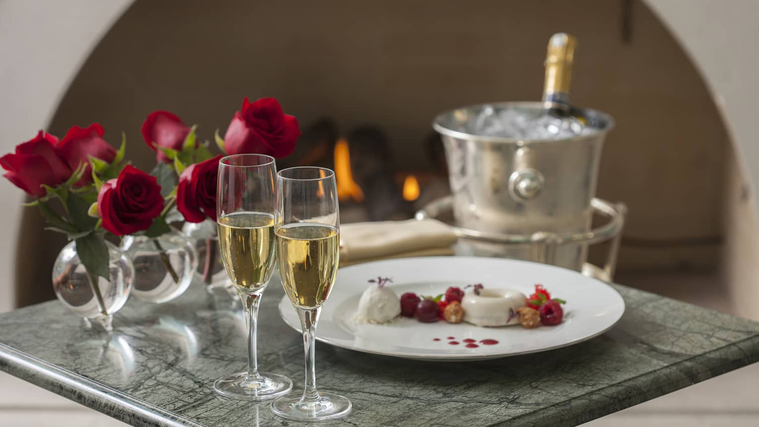 Champagne glasses and bottle on ice, red roses and gourmet dessert on tray
