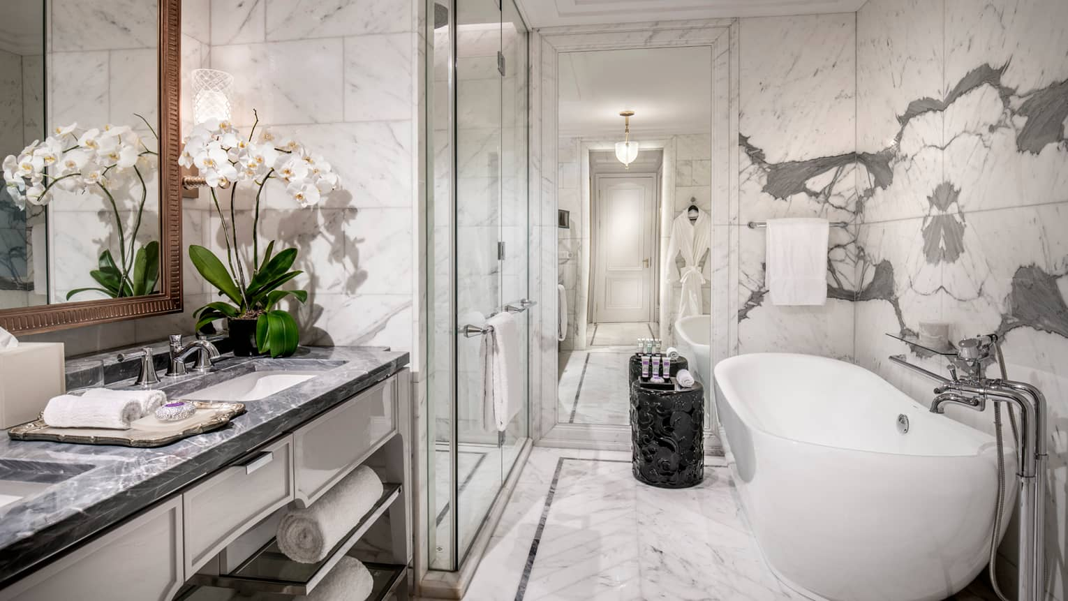 Modern bathroom with grey marble counters, white orchids in vase, glass shower