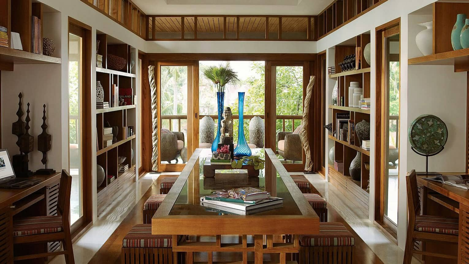 Library with wood shelves, centre table with books, decorative vases