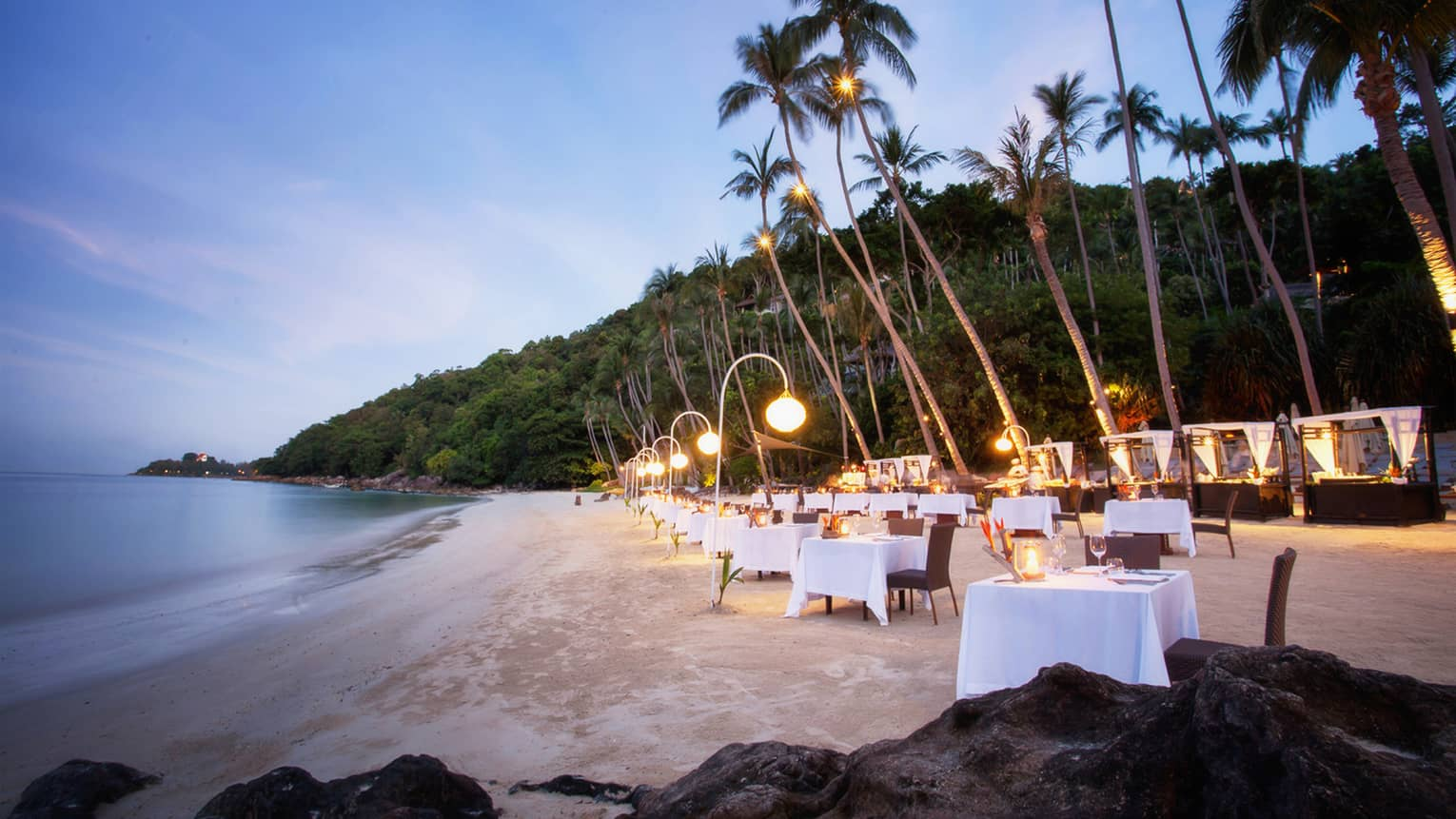 Dining tables set up along white sand beach under palm trees at dusk