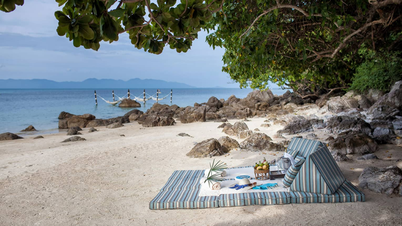 Striped cushions on white sand beach under tree with hat, fresh fruit, towels