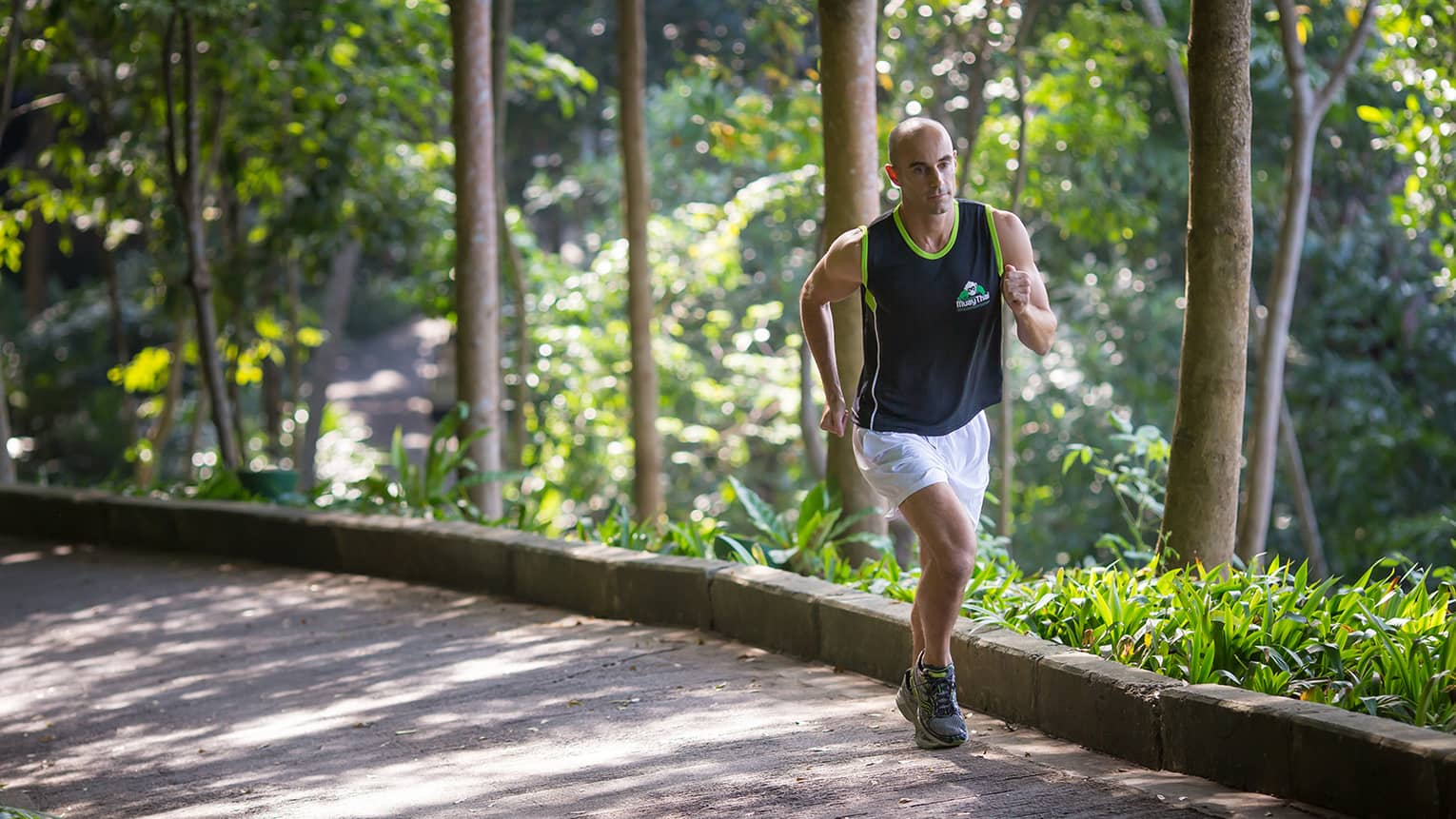 Man in workout shirt, shorts runs up pathway by trees on sunny day