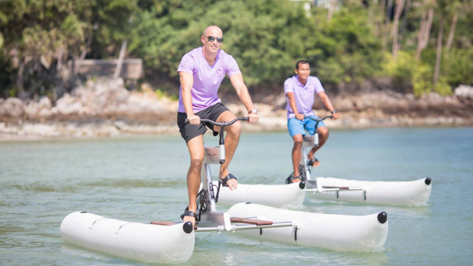 Two people wearing sunglasses pedal large white water-bike pontoons on ocean