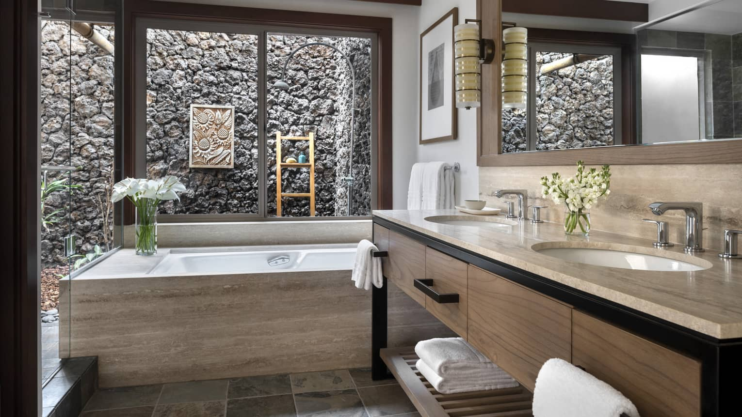 Bathroom with taupe marble vanity and tub, window looks out to outdoor stone shower