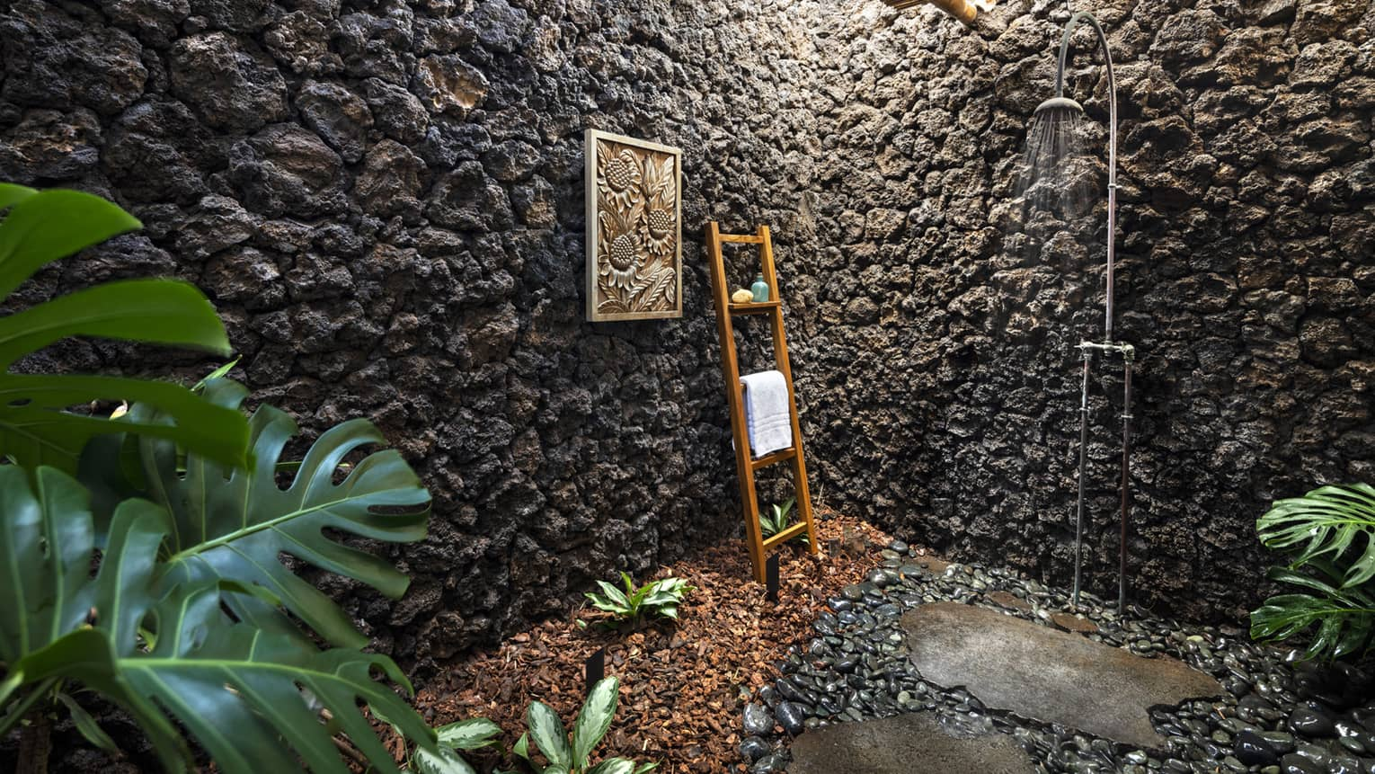 Outdoor shower with stone walls, teak ladder holding towel, greenery