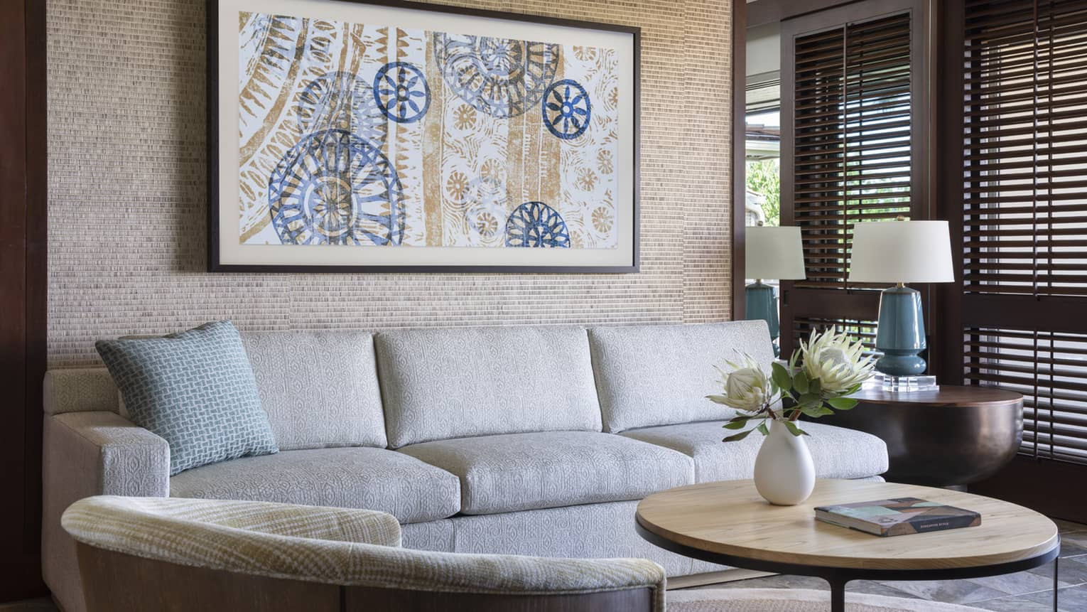 Living room with beige sofa, arm chair, round coffee table, artwork on wall, lamp