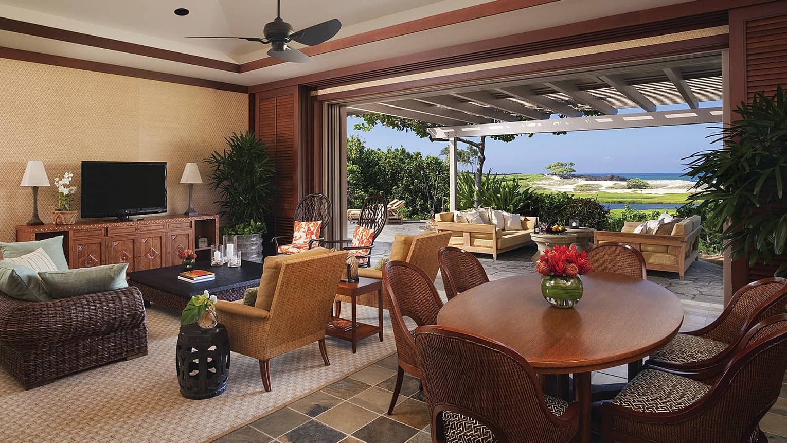 An open villa with a dining tabel and television in Hualalai, Hawaii