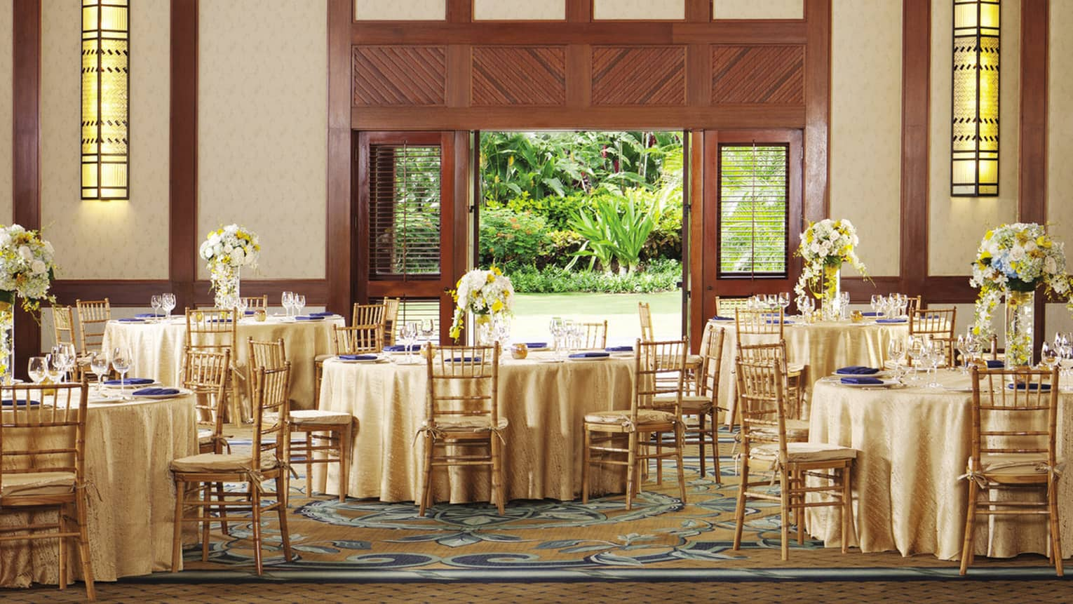 Hualalai ballroom with round banquet dining tables under high ceilings, open door to garden