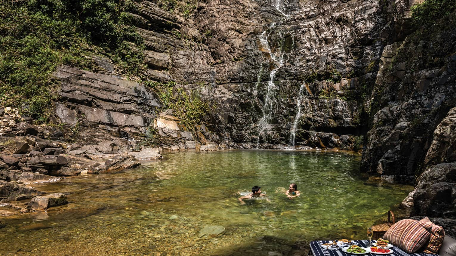 Couple swims in pool at base of waterfall, picnic lunch on rocks