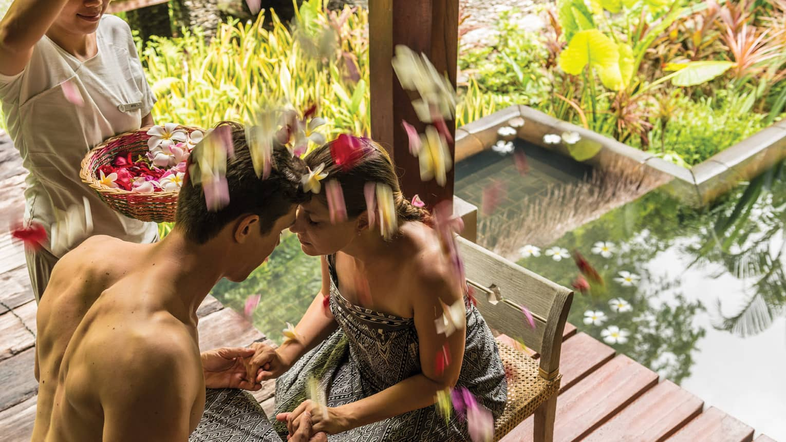 Couple on chairs, hold hands, foreheads together as woman sprinkles flower petals