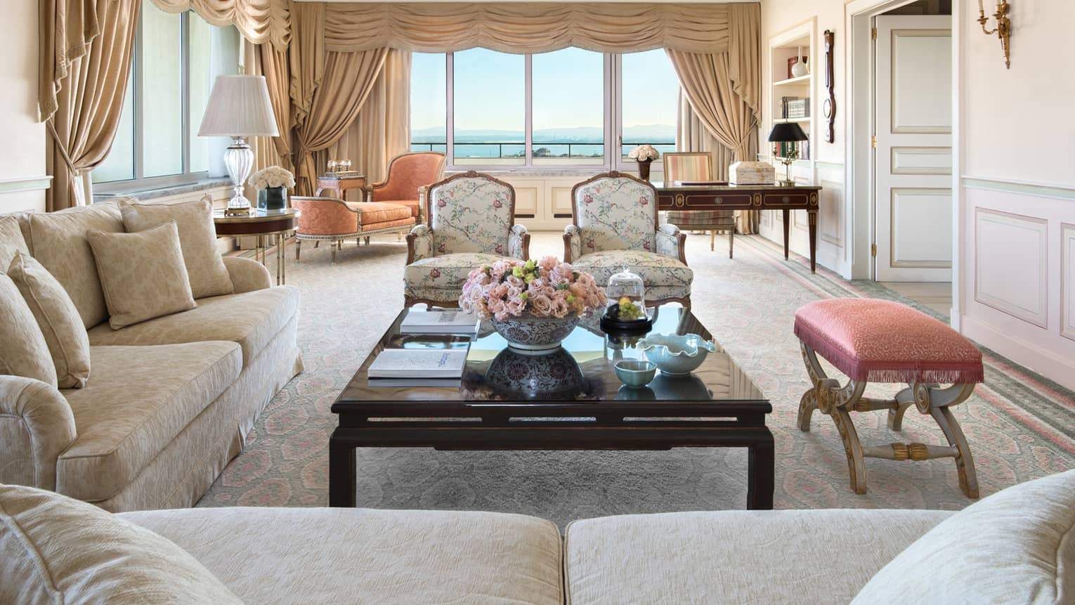 Side view of Presidential Suite seating area, coffee table, bench, two wing chairs, orange chaise, tall windows with views