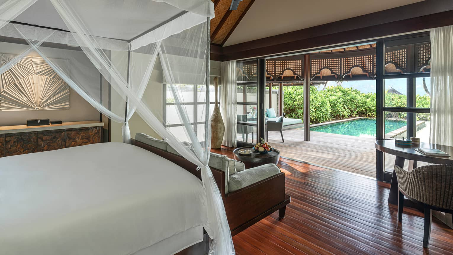 A white canopy hangs from the ceiling, covering a dark wood bed that overlooks a private pool surrounded by lush vegetation in the Sunset Beach Bungalow