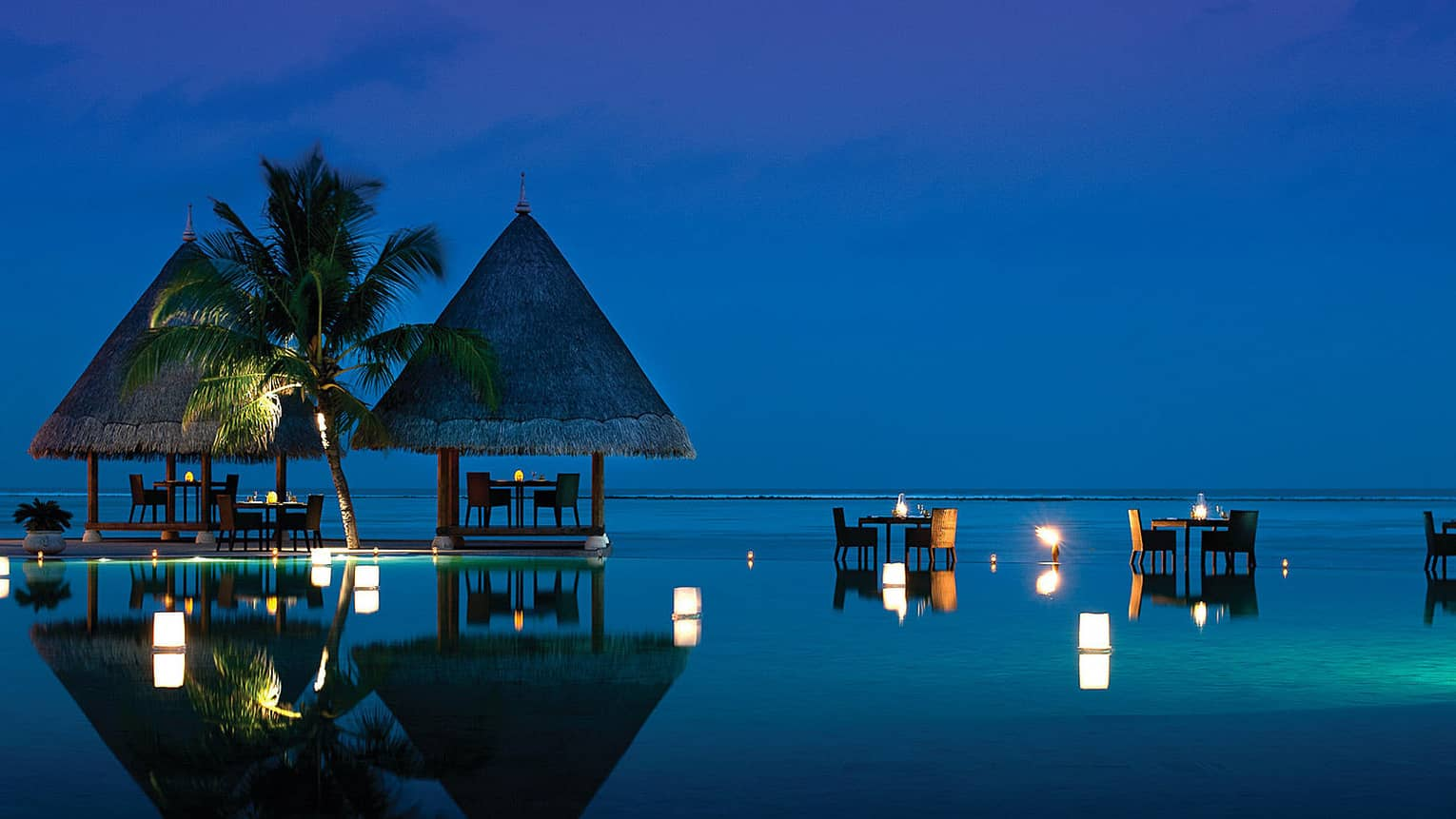 Kandu Grill at night, with candlelit dining tables under a towering palm, perched on ocean and infinity pool